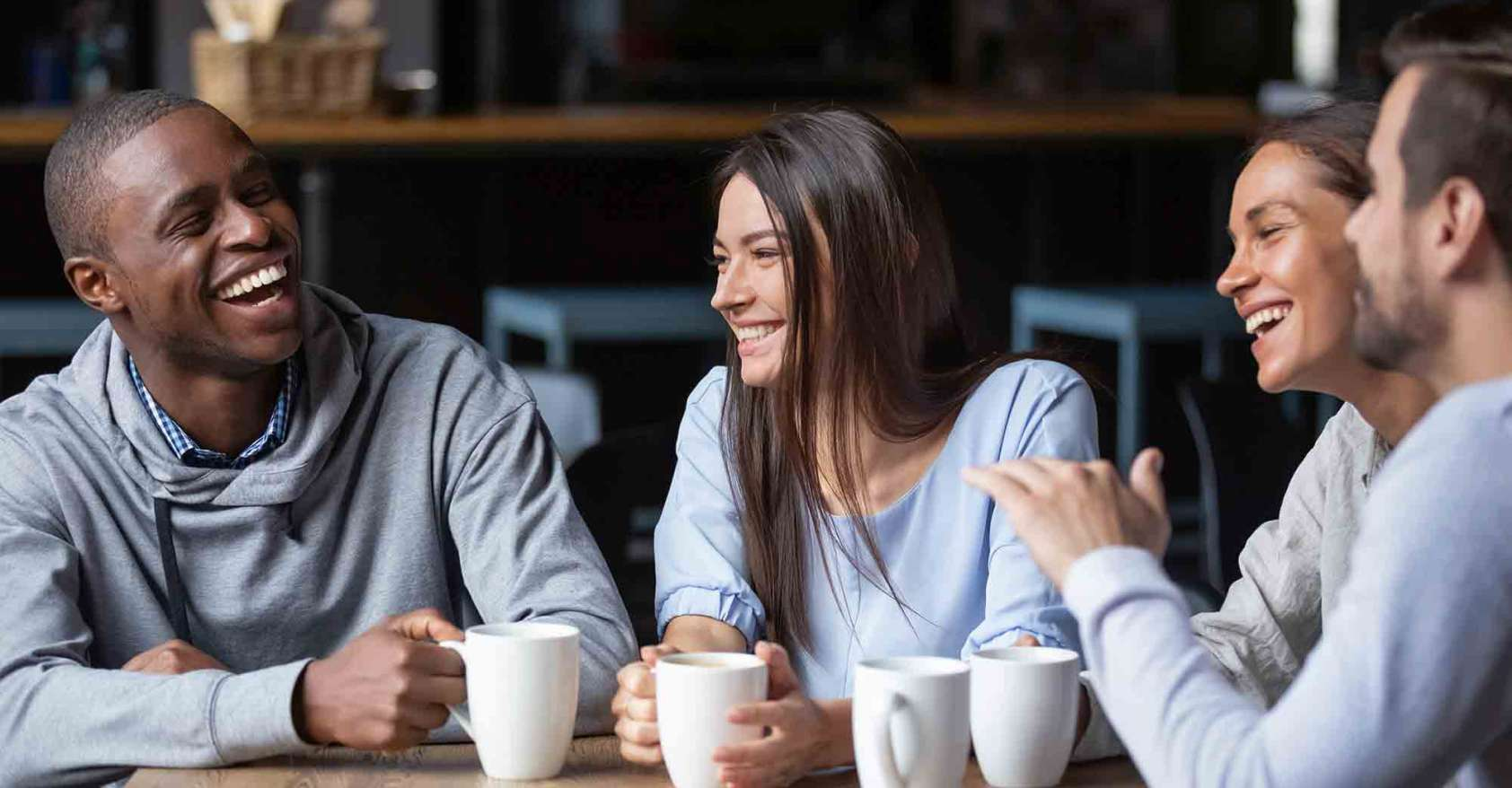 Four People Sitting at a table drinking coffee and smiling and telling stories