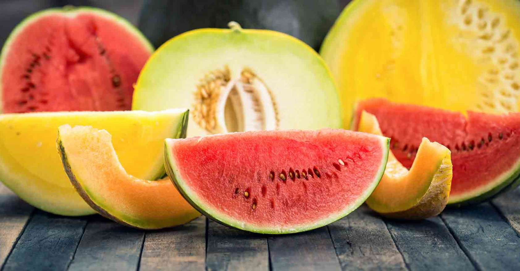 Watermelon, honeydew and canteloupe wedges and halves on wooden table pollen allergies