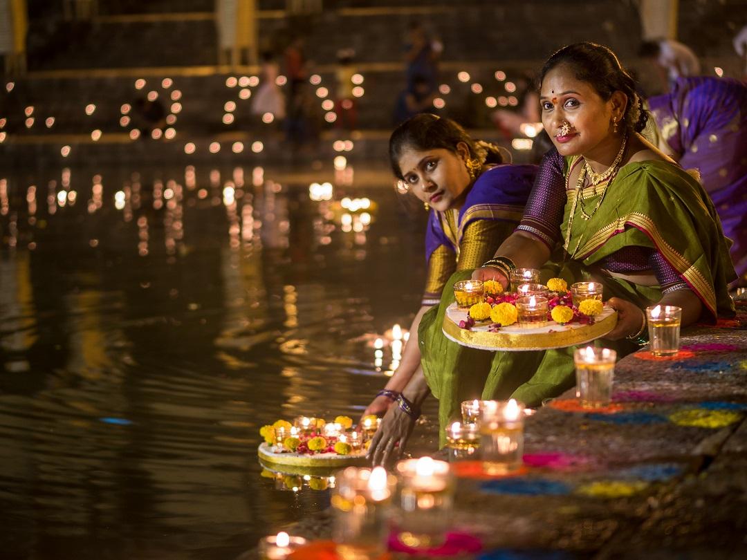 Traditional Indian woman lighting Diya during Diwali Festival in India