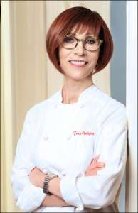 Female chef in her white coat leaning on a wall. She is wearing glasses and smiling. Fran Costigan vegan desserts