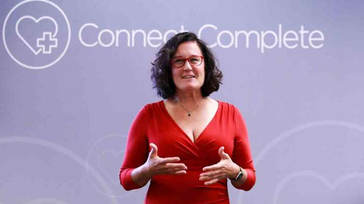 Video & Audio Resource Files Tracy Stuckrath in a red dress in front of a lavender wall