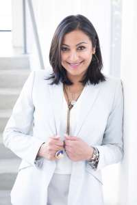 Smiling woman with shoulder length black hair in a white suit leaning on a white wall Dee Patel Committed to Community