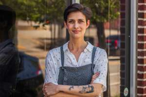 Woman with short brown hair standing with her arms crossed in front of restaurant. She is wearing overalls. Jen Hidinger-Kendrick Eating at a Meeting Giving Kitchen