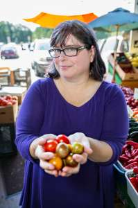 Women in purple shirt holding a handful of tomatoes at a farmers market. Kathy Hester plant-based eating