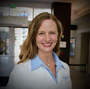 Woman with long blonde brown hair smiling. She is wearing a light blue collared shirt and a white doctor's coat while she stands in a building lobby Dr. Sabrina empower food as fuel