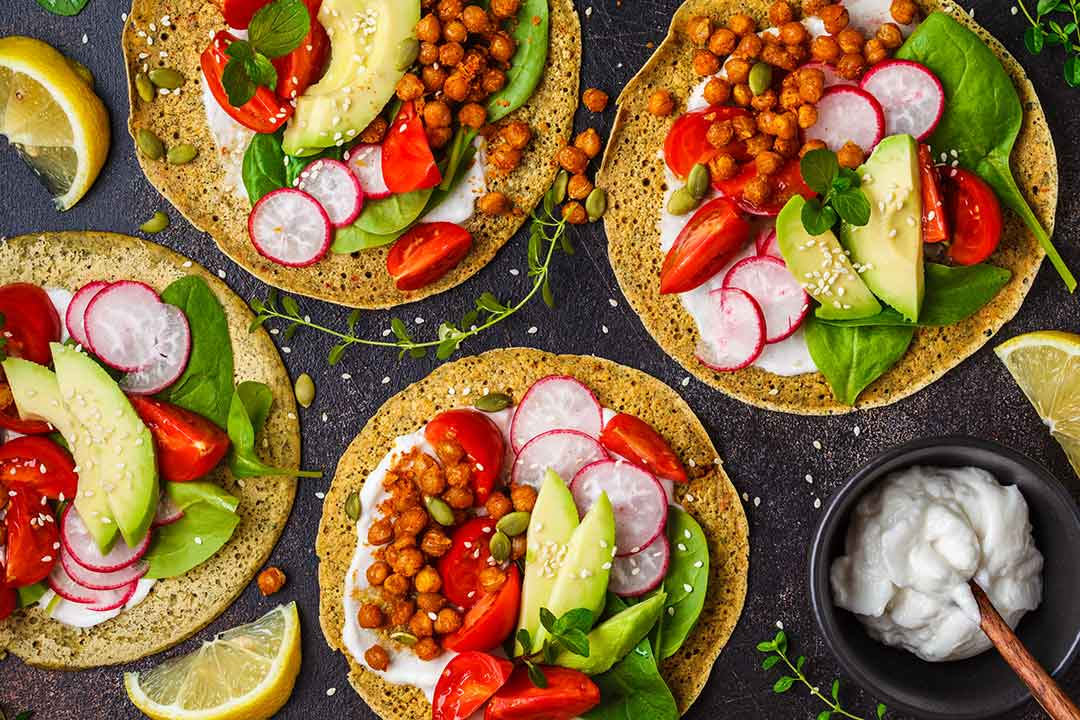 Vegan tacos with baked chickpeas, avocado, sauce and vegetables on dark background, top view — vegetarians vegetarianism