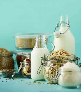 Glass bottles vegan plant milk and almonds, nuts, coconut, hemp seed milk on blue background Dairy free milk substitute 1149545076 parfaits.jpg