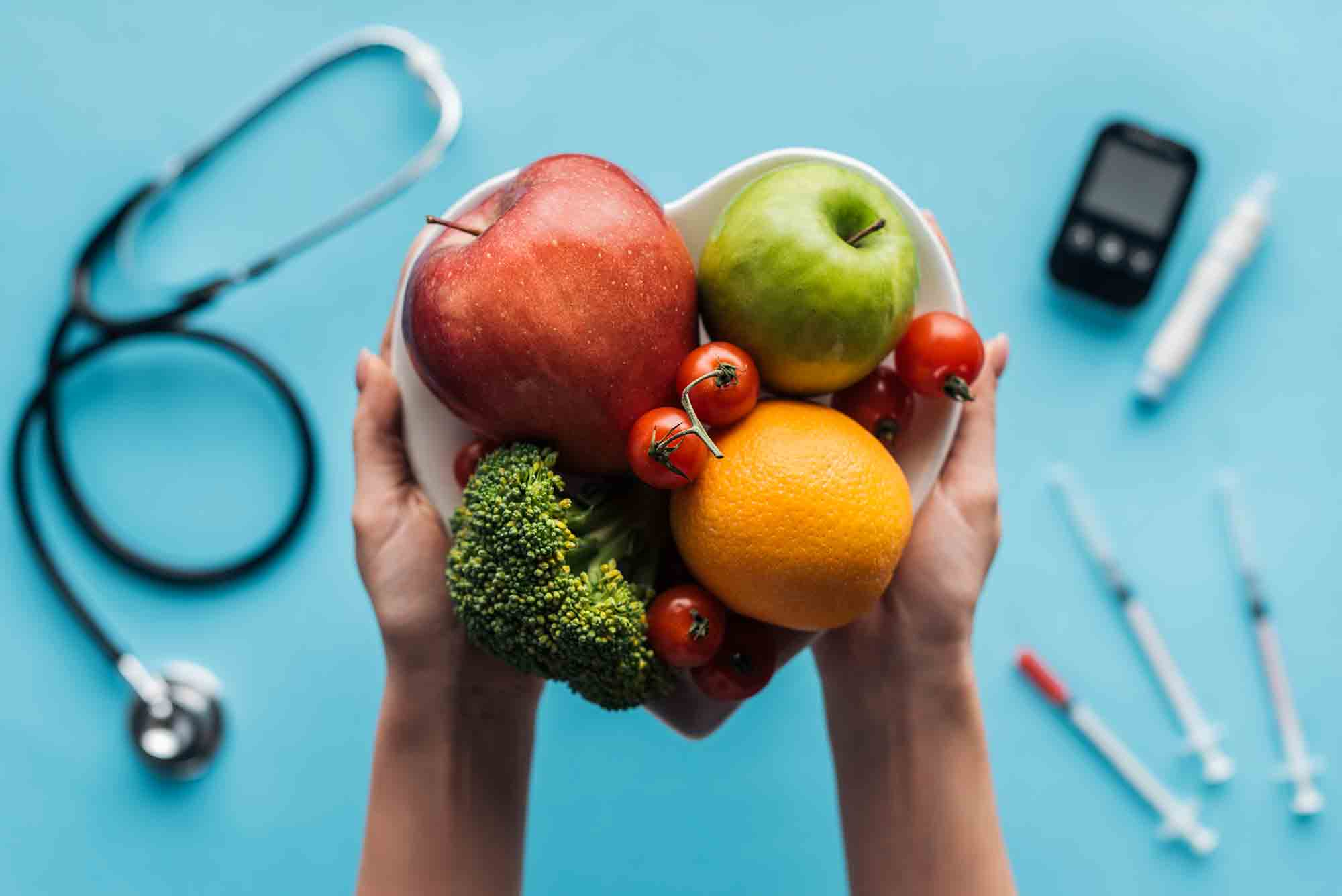 fruits-and-vegetables-in-female-hands-with-medical-equipment-on-blue-background diabetes