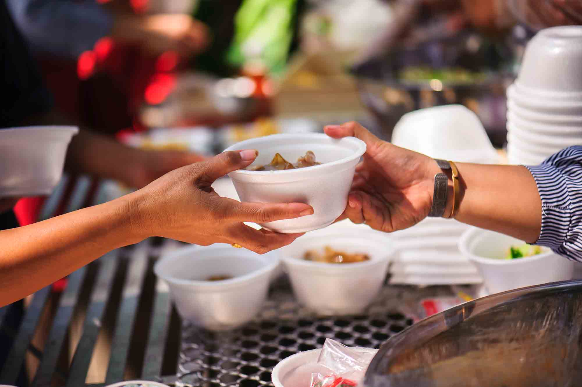 Distribute free food to the poor - two hands exchanging a bowl of food - basic human rights