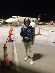 Tracy standing front of airplane with sling temporary disability