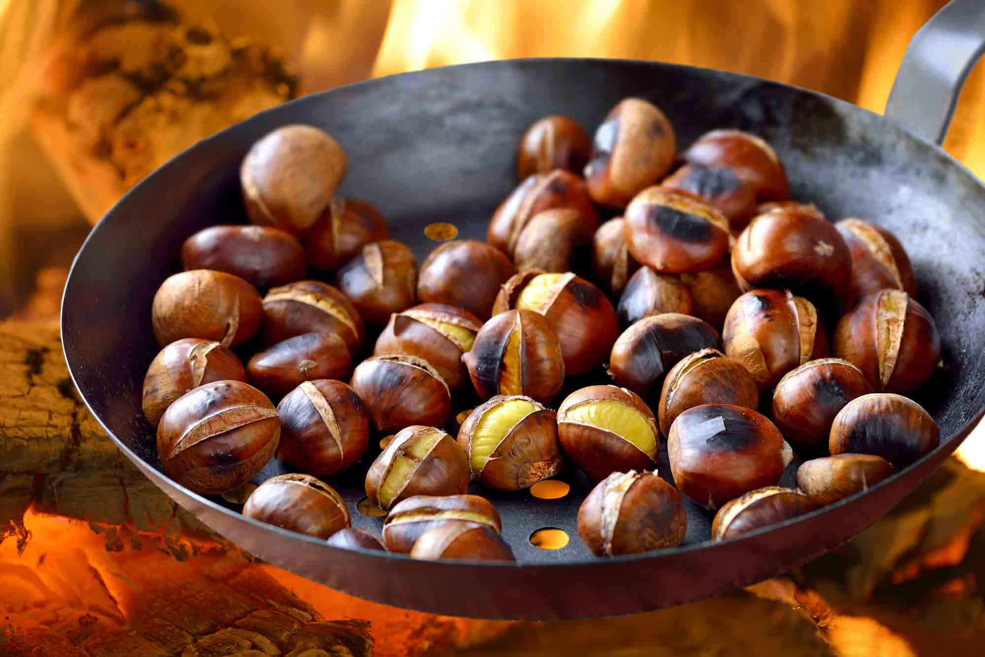 Chestnuts roasting in metal pan on an open fire nut allergy