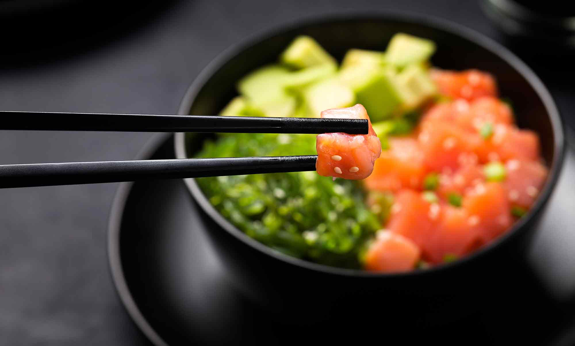 Poke with diced red fish avocado and green seaweeds salad with piece of salmon in chopsticks in foreground 2020 trends