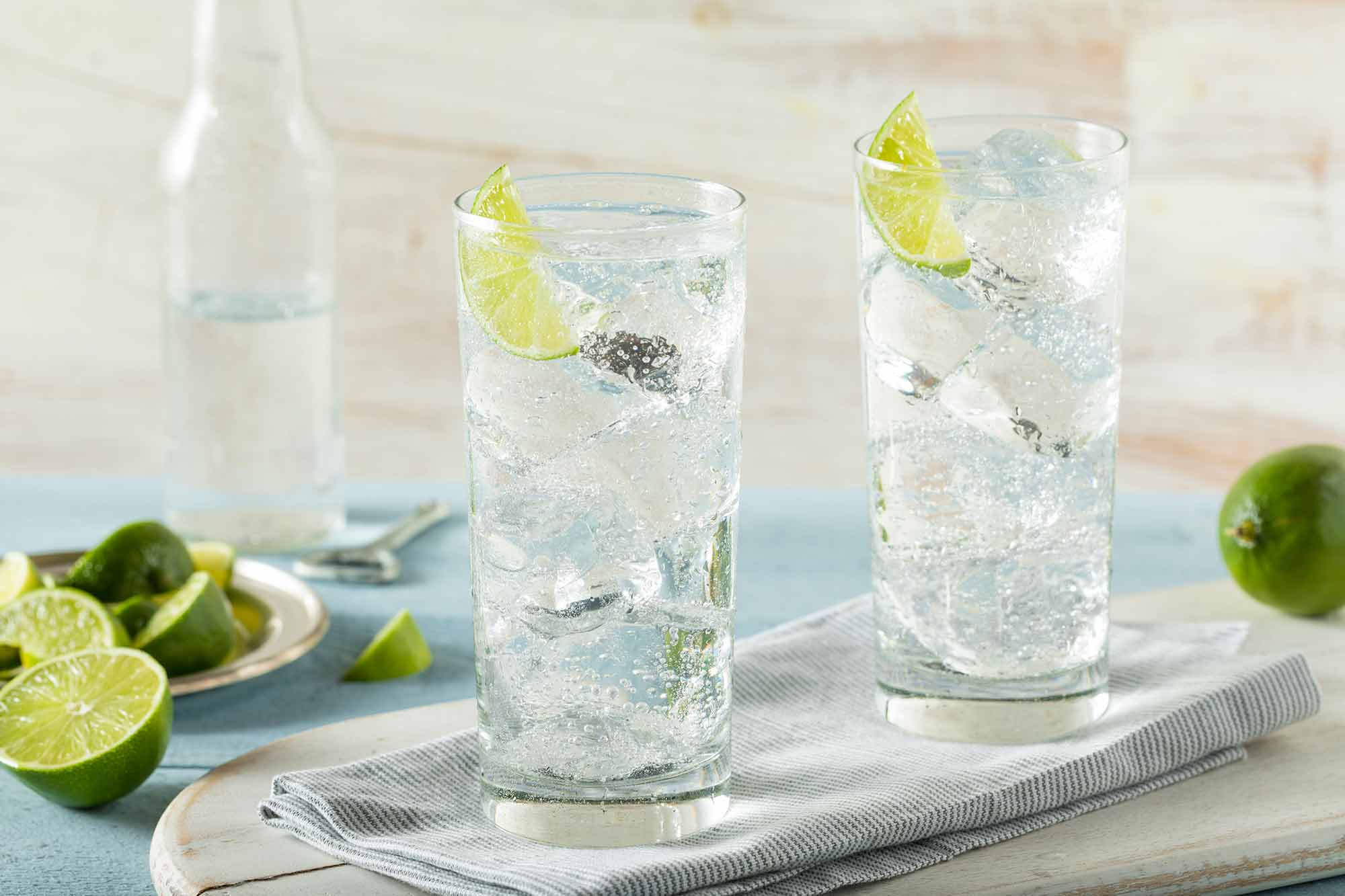 Two clear glasses of Hard Sparkling Water with limes on a tray Drynuary