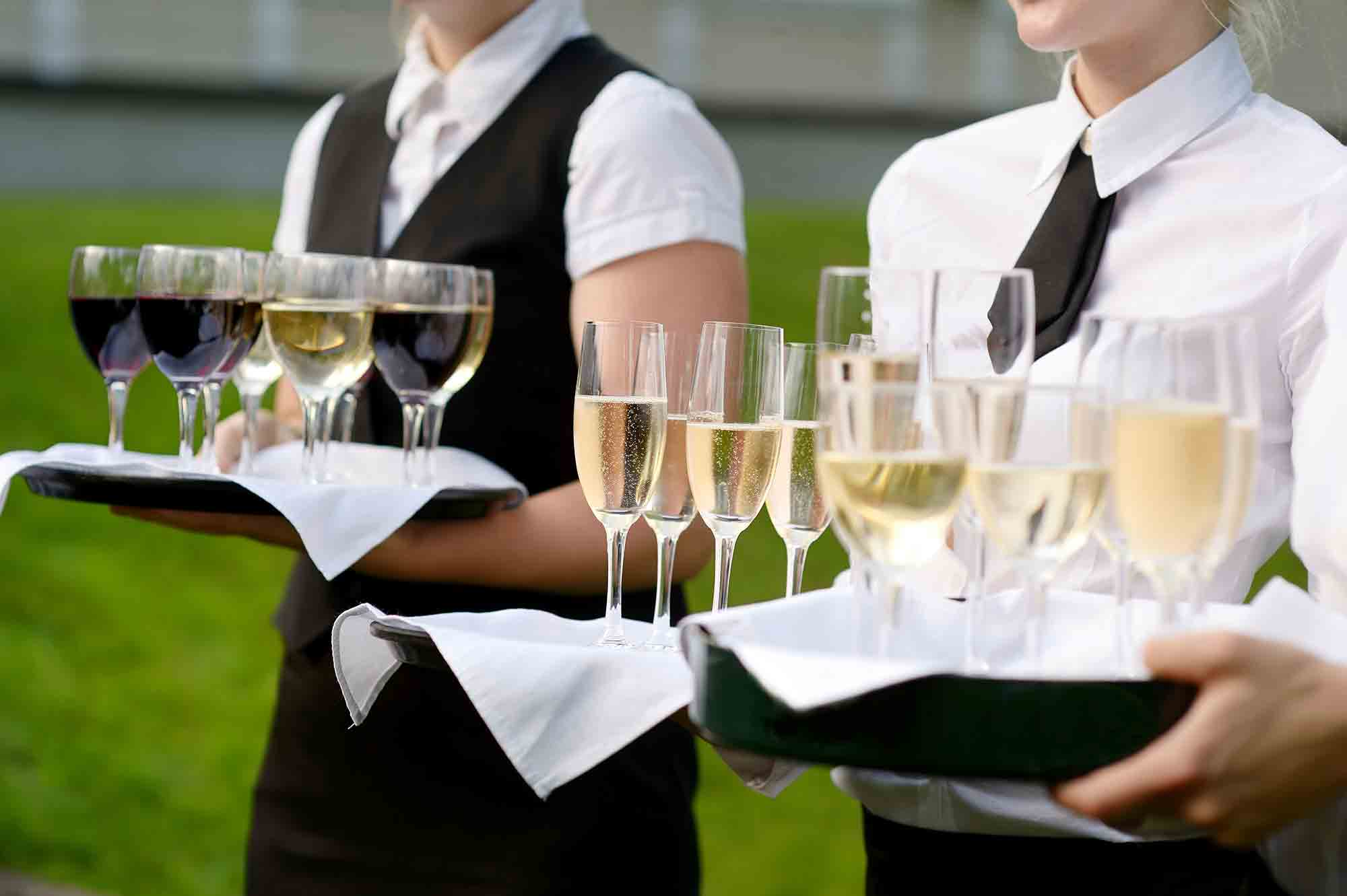 Close-up of 3 Waitresses standing in a field holding platters of wine and champaign. drinking