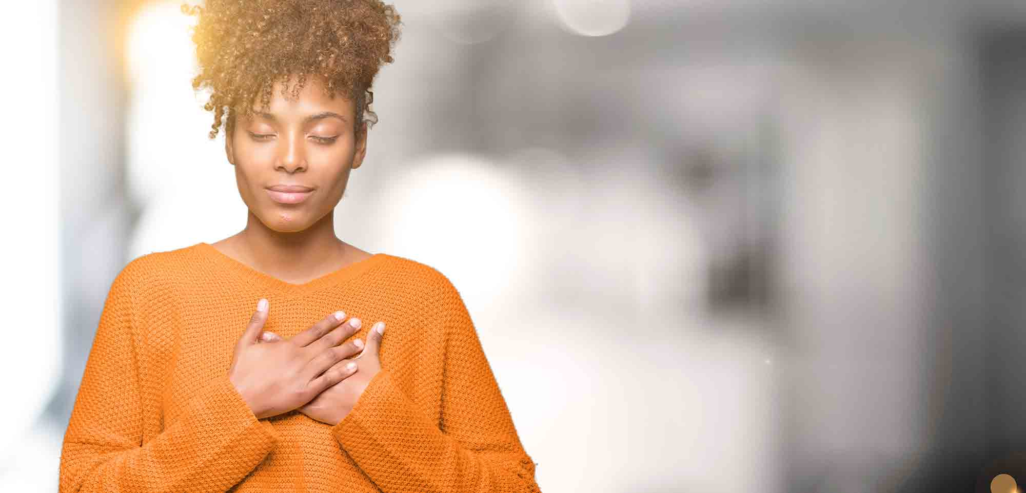 black woman in orange sweater with her hands on her heart self care