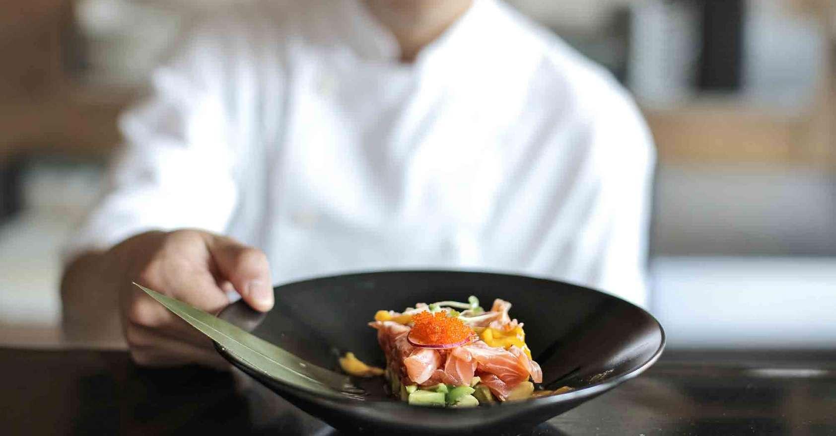 Chef showing plate with fish tartare coronavirus