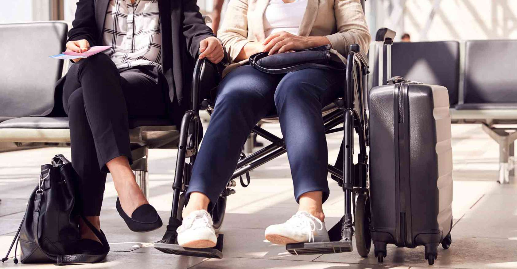 two women sitting in airport one in a wheelchair personal care assistant