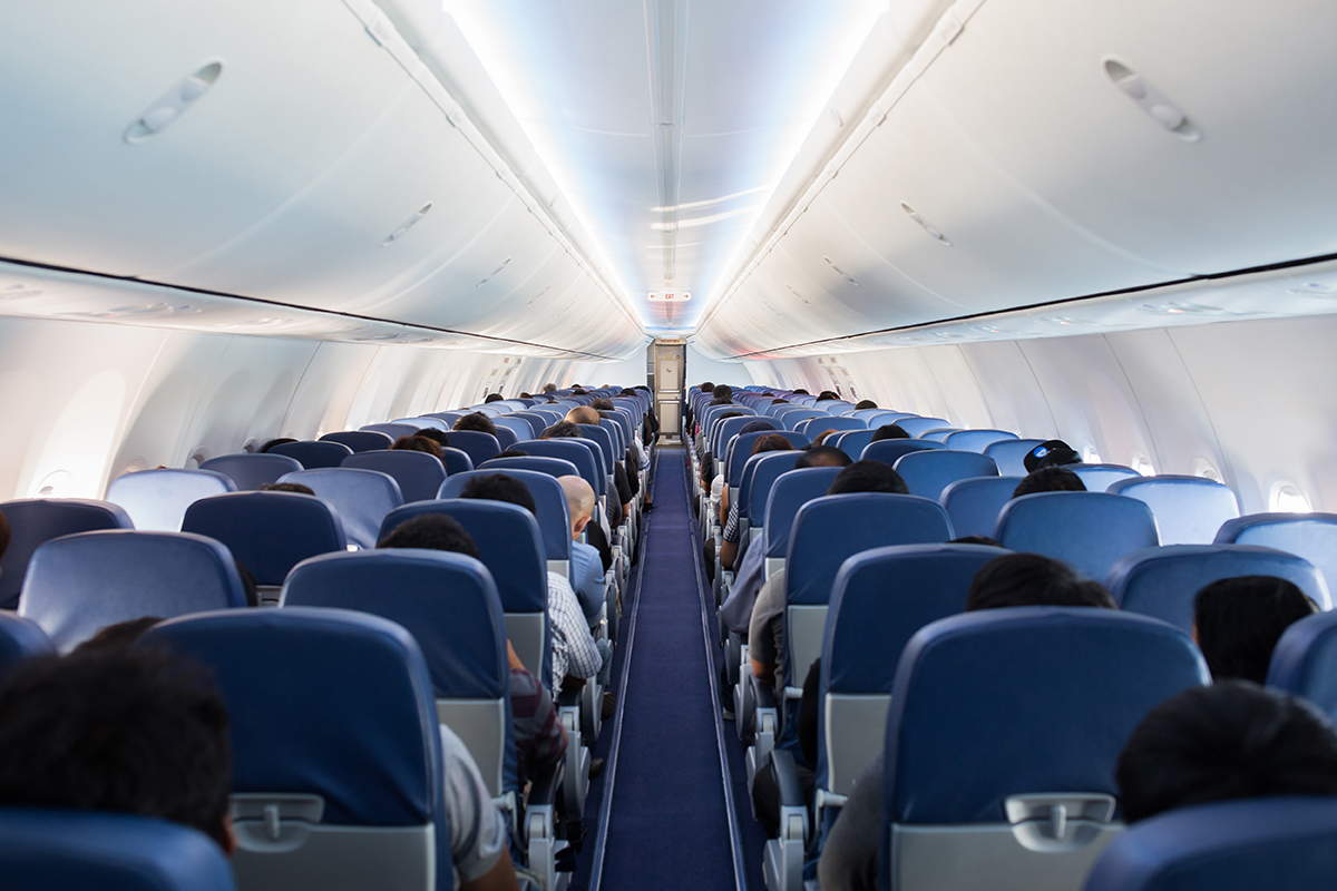 blue Airplane seats from behind people are seated in them airline