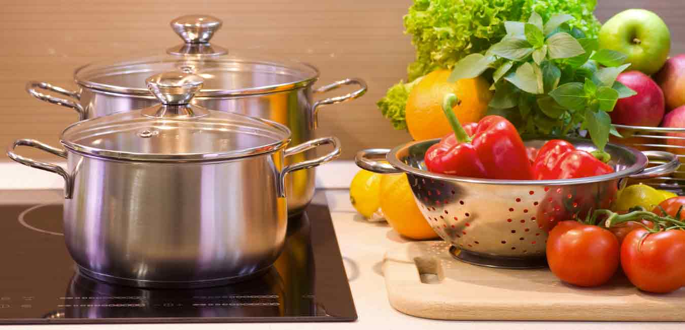 two silver stock pots on a stove with colander and cutting board full of fresh vegetables empower fuel delicious