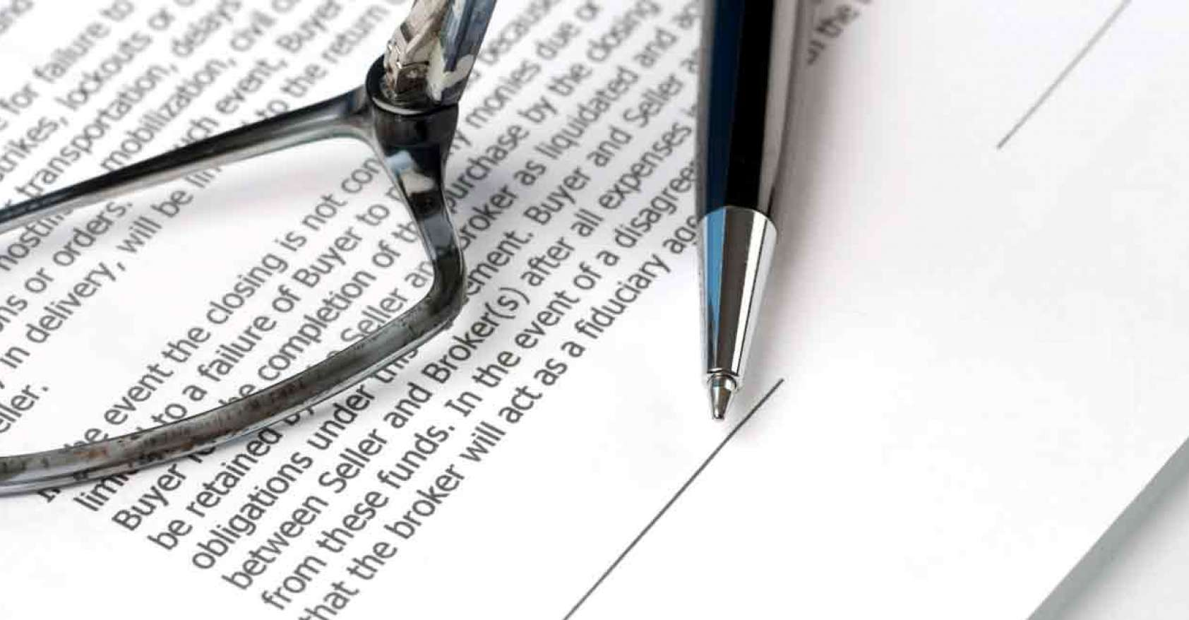a contract with a pair of glasses and a pen on top for the topic of contracting F&B