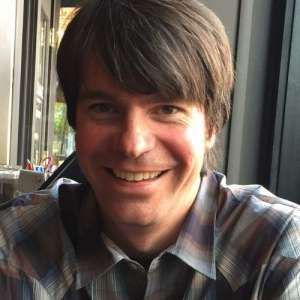 Close-up of a smiling man with brown hair wearing a plaid shirt. He is sitting in a restaurant with windows behind him. He is an expert in food Safety and sustainability