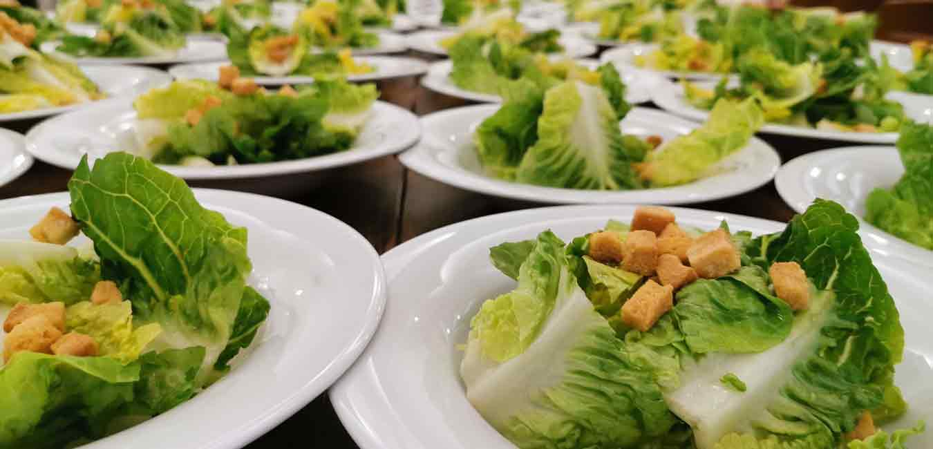 Lettuce and croutons on multiple white plates food costs