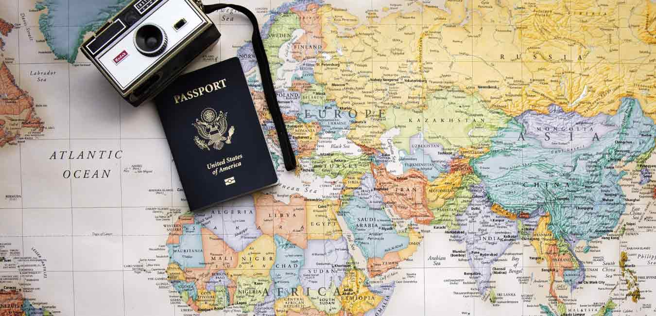Picture of a world map with a passport and camera on top to travel confidently with food allergies Allie Bahn
