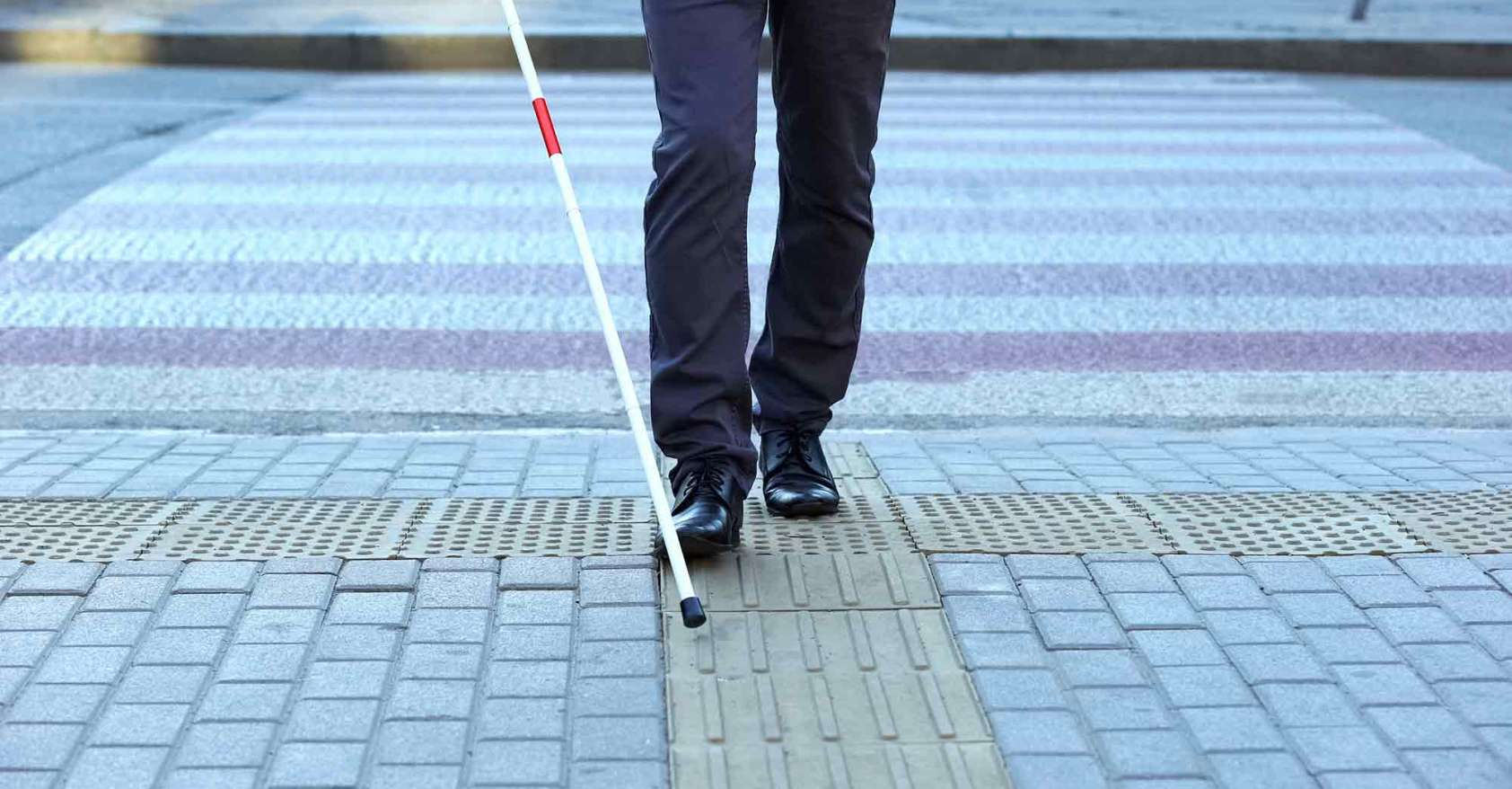 Visually impaired man using tactile tiles to navigate city, finishing crossroad Disability diplomat