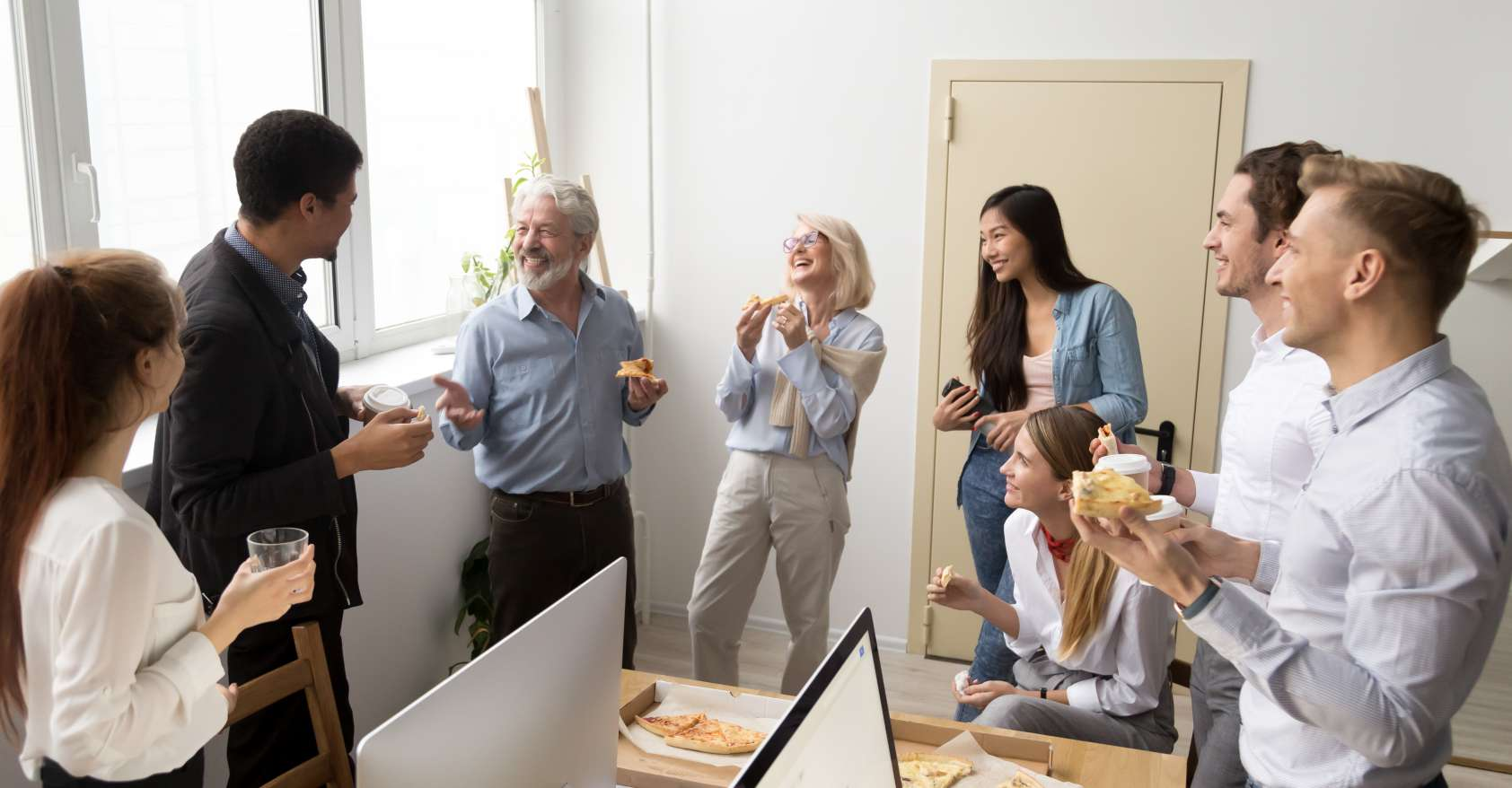 Friendly diverse business team talking and laughing eating pizza together promoting workplace culture