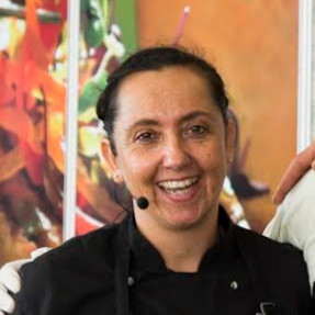 Smiling woman in a black chef coat