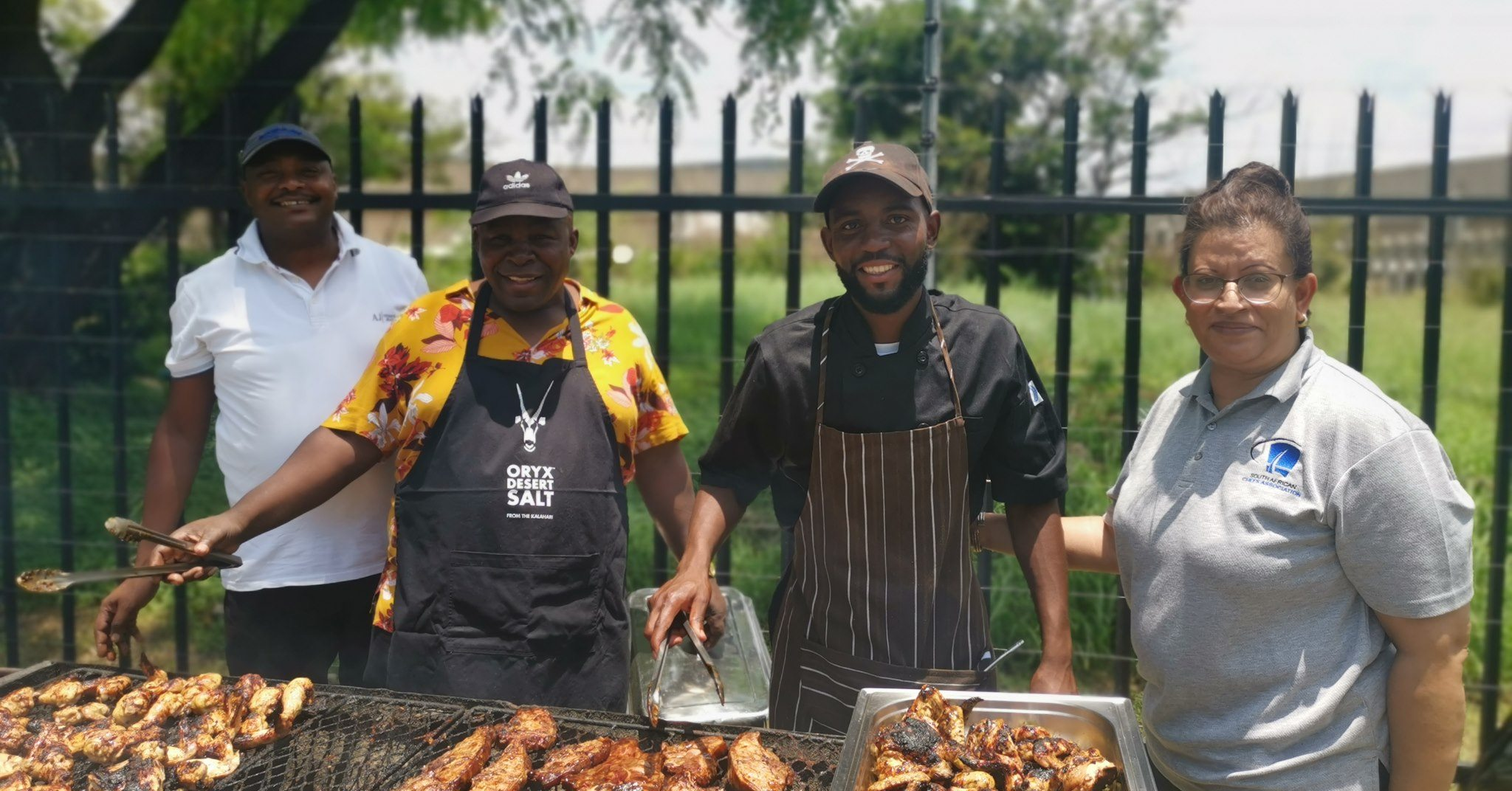 Three men and one standing behind a grill cooking food to give to those in need