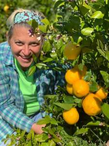 Smiling woman in a blue striped shirt and green t-shirt standing behind an orange tree. She runs Farm to Pantry