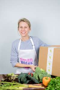 smiling woman behind a table full of vegetables and holding a box; CEO of Small Bites Adventure Club