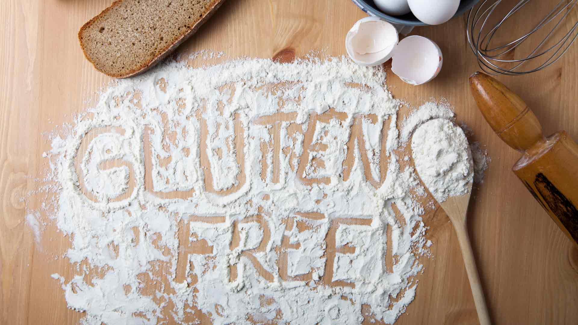 The words Gluten Free written in flour on a wooden table Gluten-free Watchdog