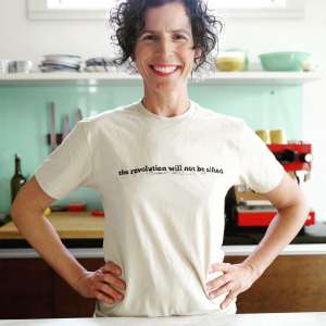 Smiling woman standing in a kitchen with her hands on her hips. She is The Grain Lady