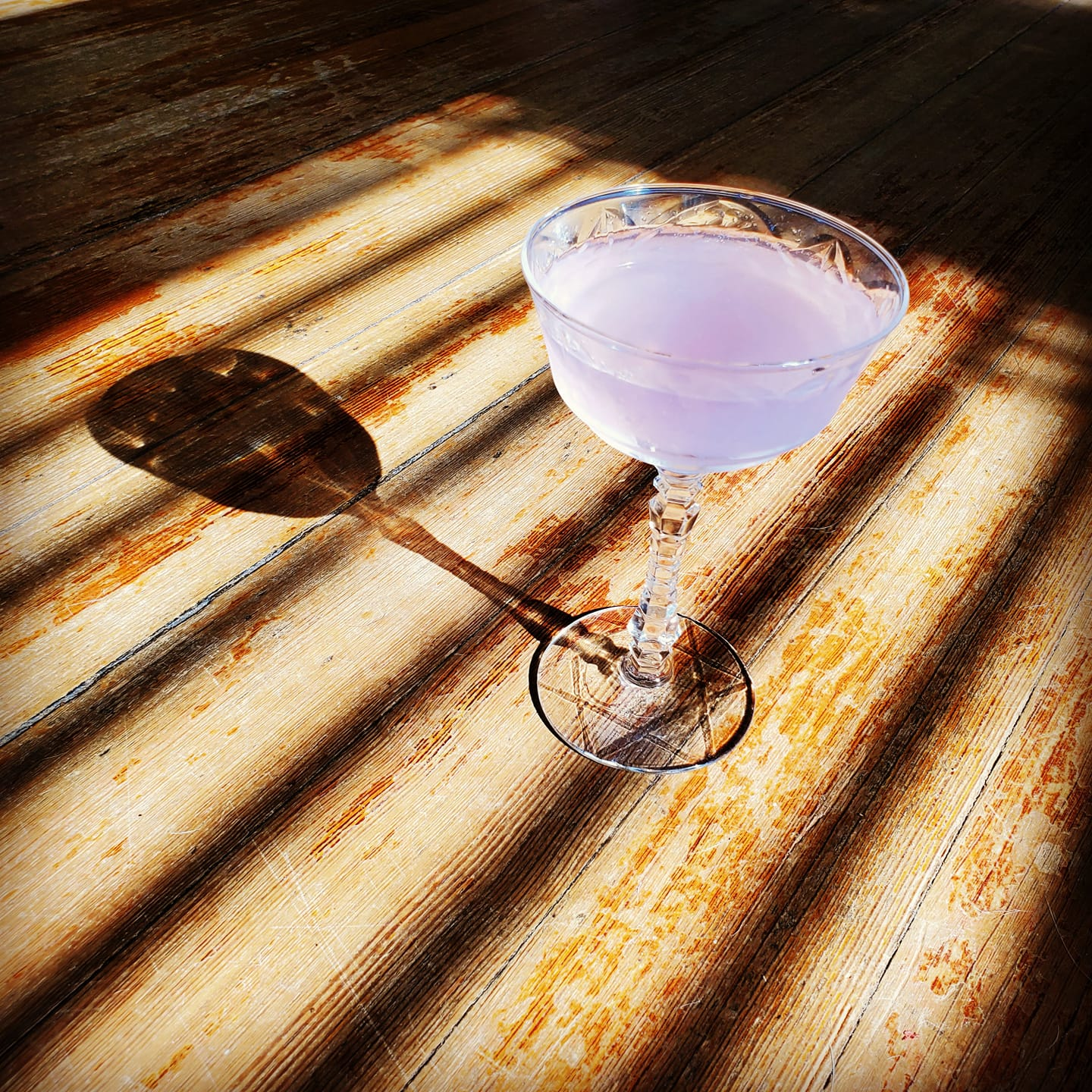 A single cocktail on a wooden deck its shadow to the left made by bartender Tiffanie Barriere who provides history lessons with every cocktail she serves