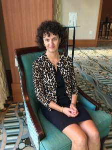 Woman in a leopard patterned sweater and black dress sitting in an aqua colored chair Gluten-free Watchdog Tricia Thompson