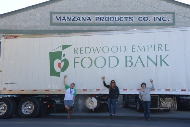 Duskie Estes and two other people standing on the side of a Redwood Empire Food Bank trunk celebrating all of the food they have glean from a local farm