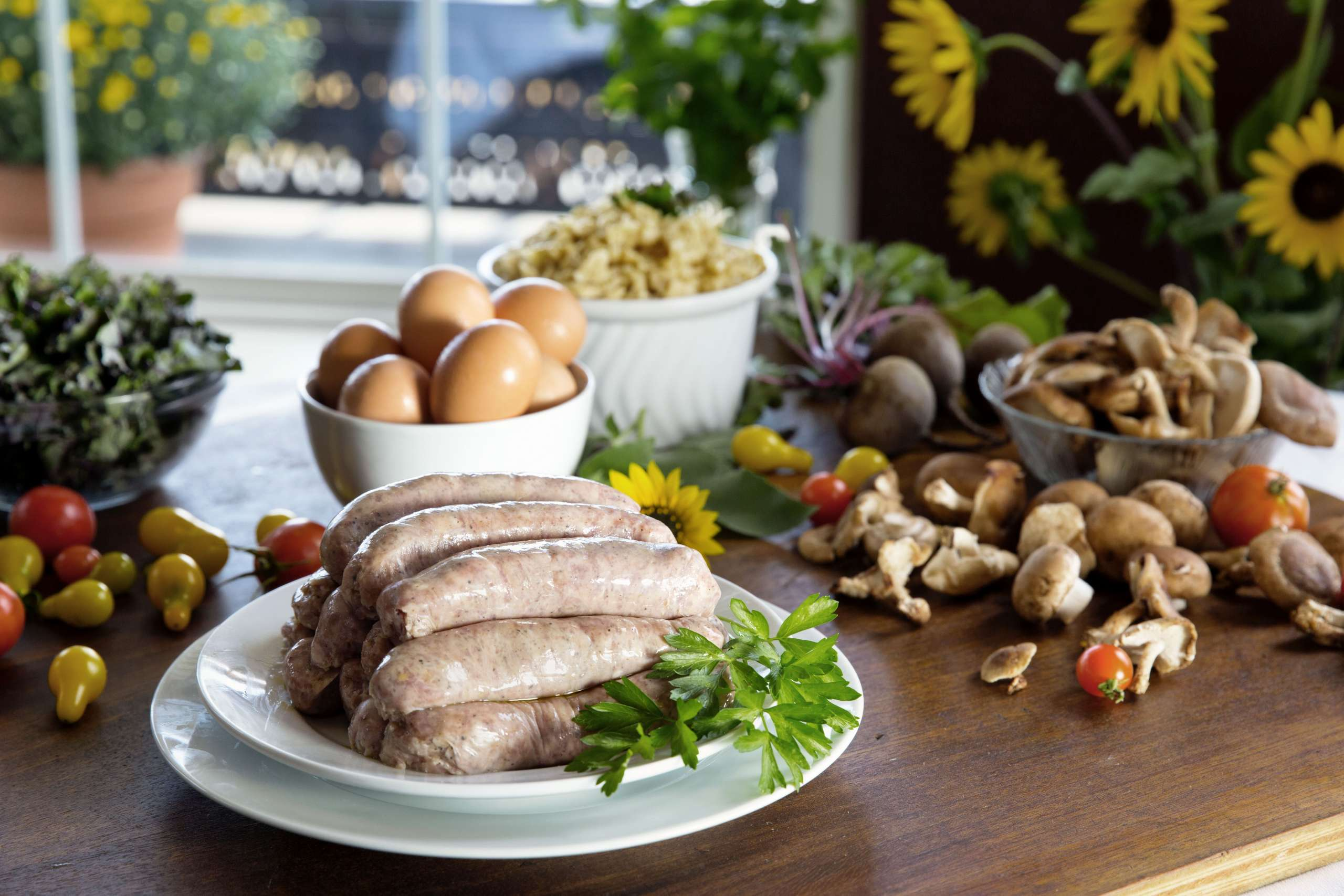 Plate with a stack of sausage on a wooden table with a bowl of eggs behind them and vegetables scattered around them