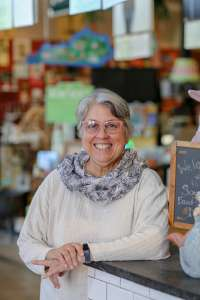 Smiling woman in a white sweater and blue scarf leaning her left arm on a counter top. She is an expert on how food is culture