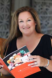 Smiling woman holding a cookbook in her hands