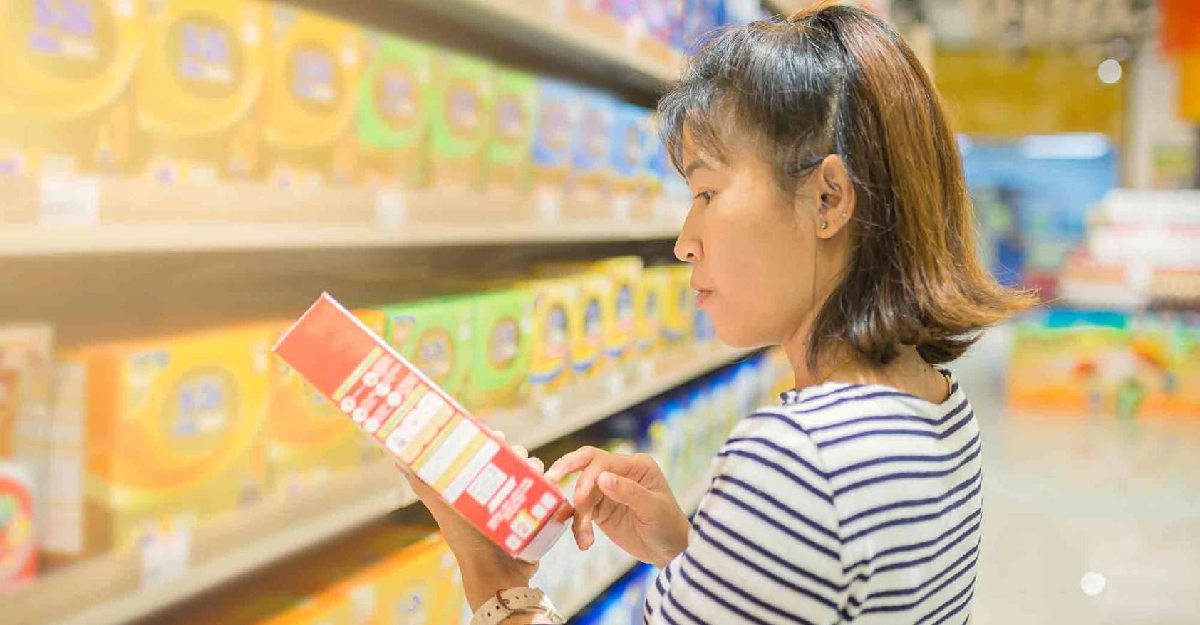 Asian Woman Reading Food label while standing grocery aisle. She managing control of what she eats