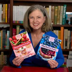 Smiling woman in a blue shirt holding the two books she just published, Cynthia Graubart