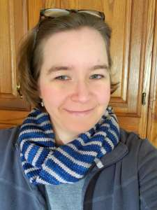 Smiling woman wearing a blue and white striped scarf over a gray jacket. She is Margaret Clegg of MI Gluten Free Gal who has celiac disease