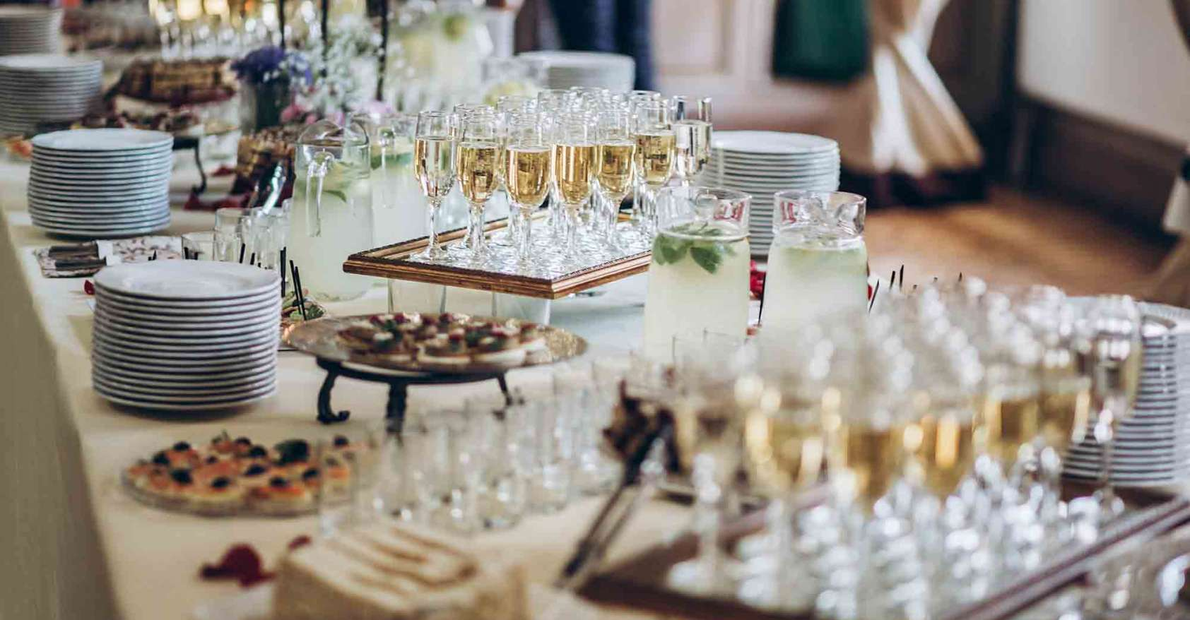 stylish champagne glasses and food appetizers on table to demonstrate how to plan menus for people with Autoimmune diseases